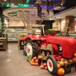 Der knallrote Porsche-Traktor im Rewe Köln inmitten der Obst- und Gemüseabteilung